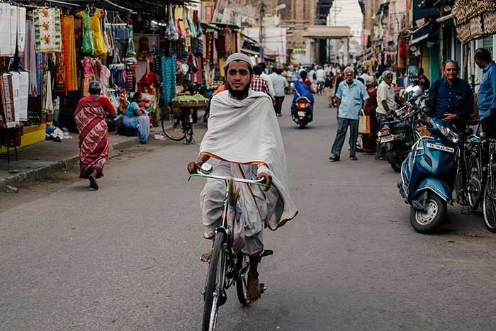 Indian man riding a bike at a flee market - face swapped in Photoshop