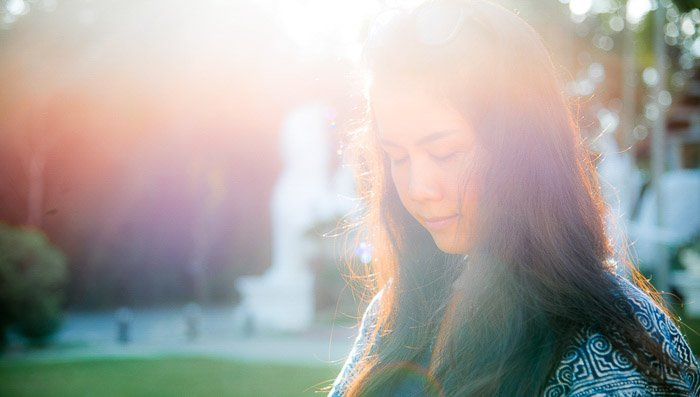 A portrait of a female model outdoors with lens flare