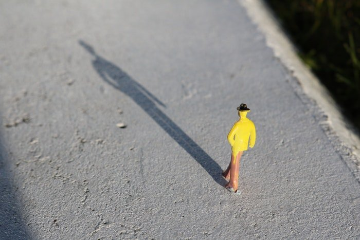 A yellow toy figure on a concrete surface