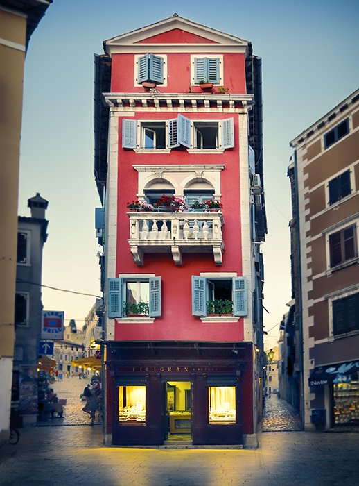 A quaint red building stands out because of its symmetry, vibrant colours, and warm lights