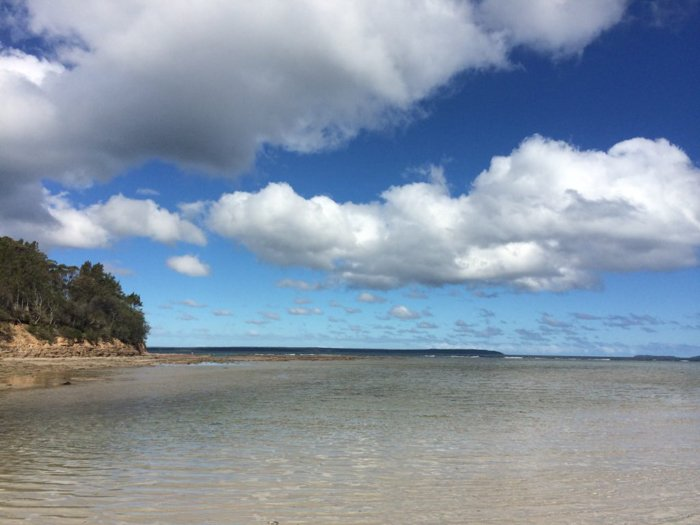 calm clear waters of beach and big clouds in blue sky