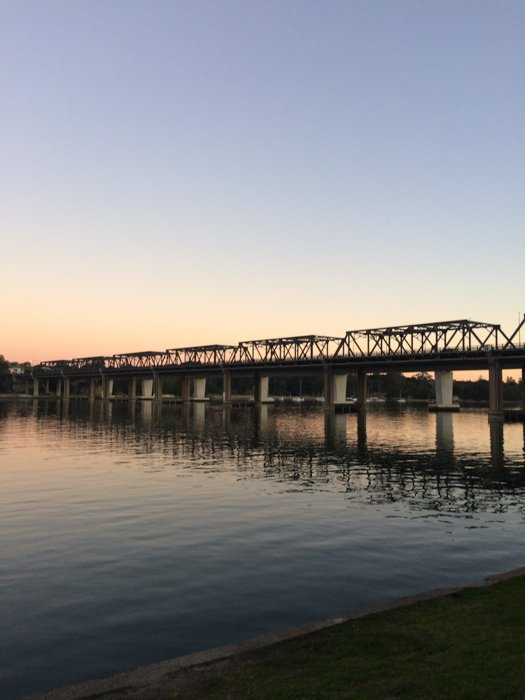 silhouette of a long bridge over water at sunset
