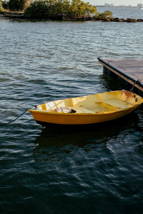 a bright yellow boat on clear deep blue waters