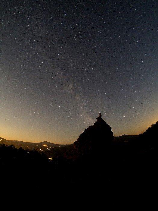 A man sitting on a rock under an impressive star filled sky