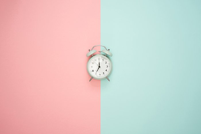 A quirky product shot of an alarm clock demonstrating symmetry in photography due to the central composition and split colour background
