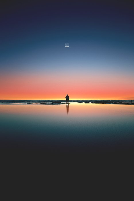 Stunning portrait of a lone figure on a beach below a colourful sunset - symmetry in photography