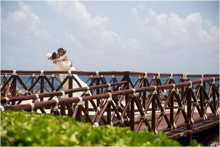 A newlywed couple embracing on a wooden bridge