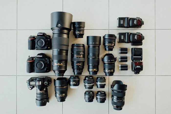 A photography flat lay of camera bodies, flashes and lenses