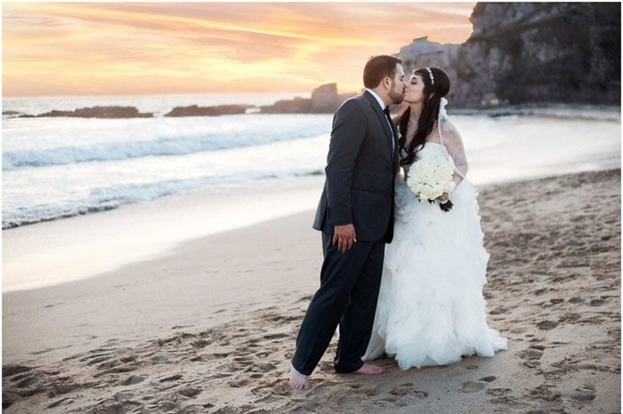 Romantic destination wedding portrait of a couple kissing on a beach