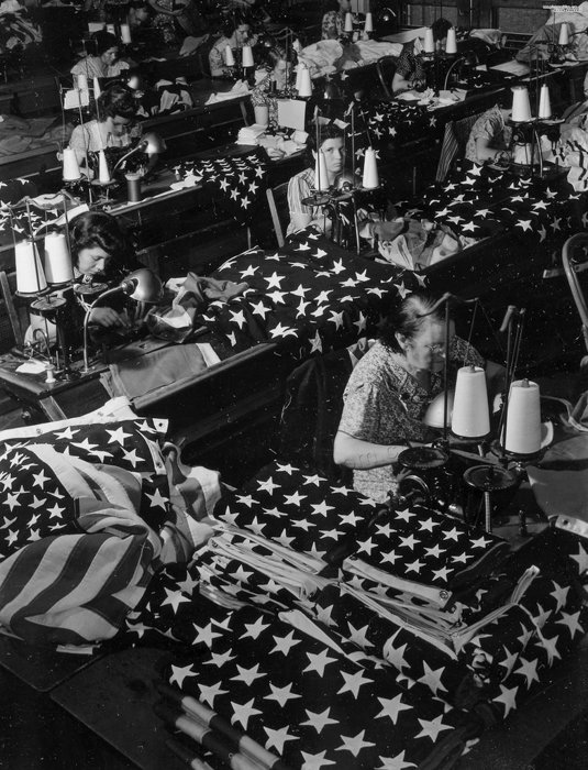 A black and white shot of women sewing american flags by war photographer Margaret Bourke-White
