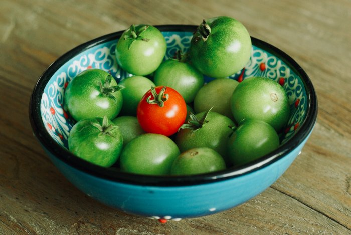 A bowl of green tomatoes with one red tomato