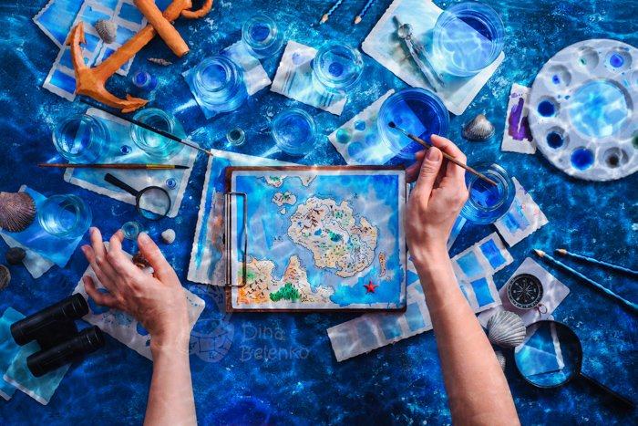 An overhead shot of a persons hands, painting a map underwater