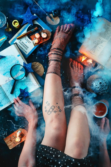 An overhead shot of a female models legs, sitting among candles, papers and other props