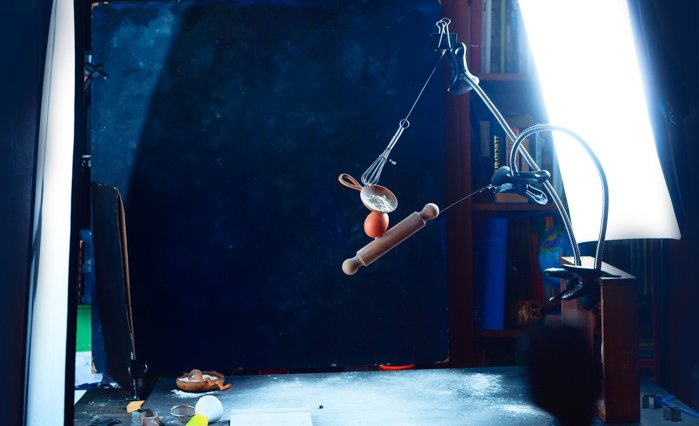 Setup for shooting a still life of a hand balancing kitchen utensils and flour clouds - creative still life photos