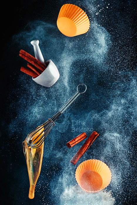 A still life shot using flying kitchen utensils and flour clouds - creative still life photography