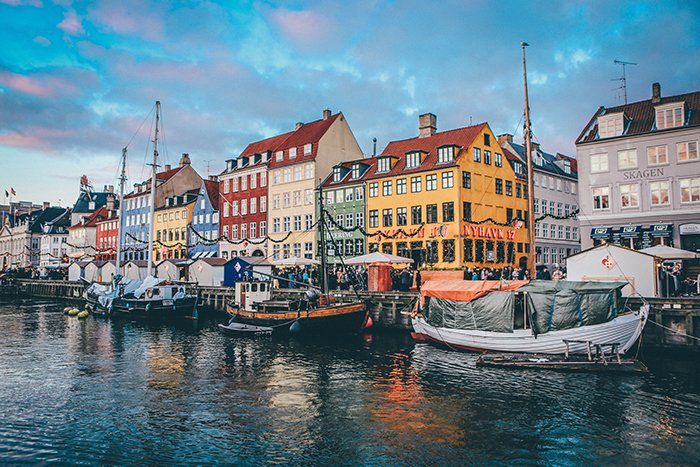 Coloured house and boats by the river in Copenhagen - most beautiful cities in the world