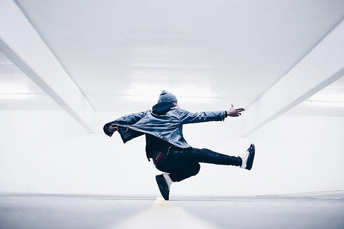 A dance photography shot of a male dancer mid jump