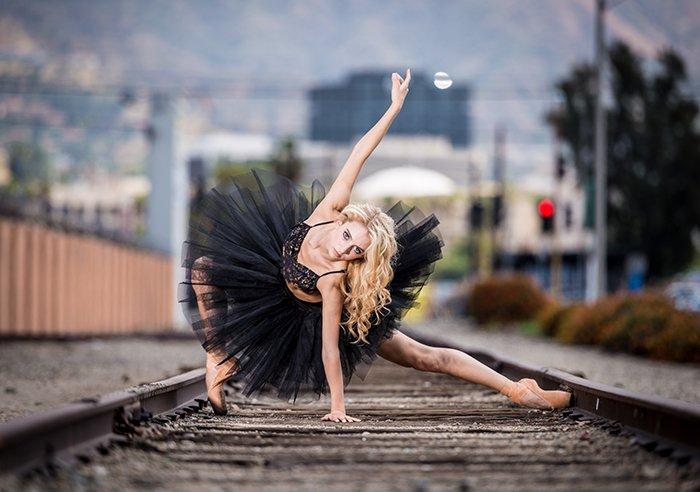 An atmospheric dance portrait of a female dancer on train tracks