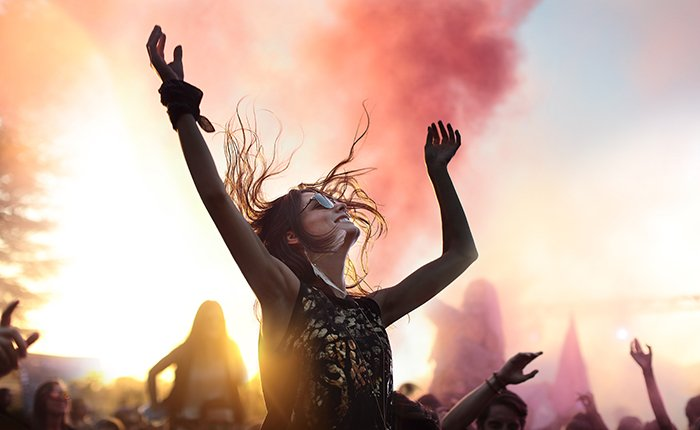 A portrait of a female dancing at an outdoor event at sunset