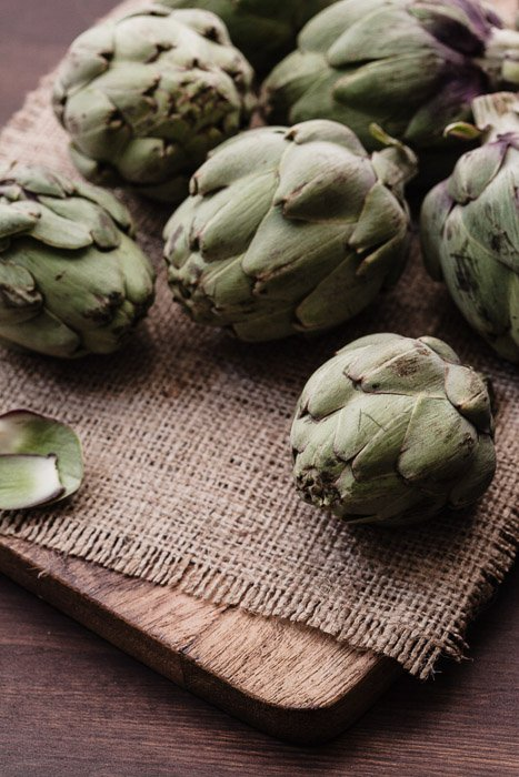 A close up of artichokes on a rustic burlap and wooden background