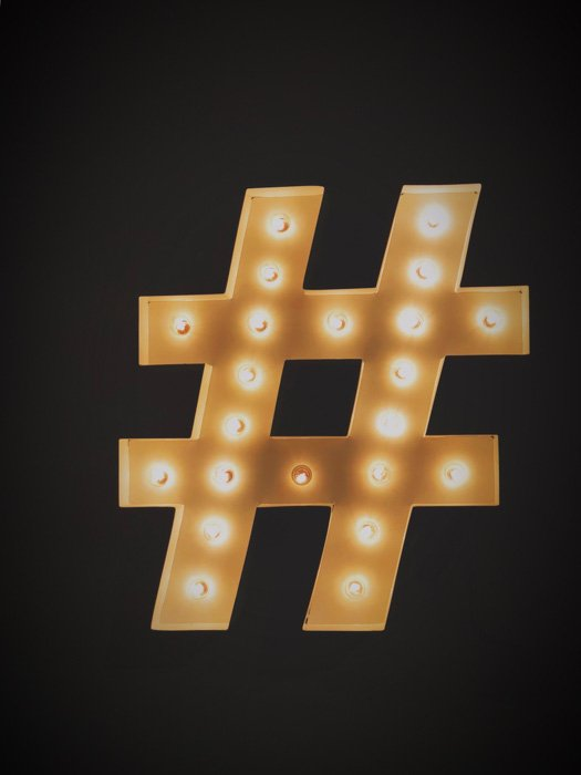 A golden lighted Instagram hashtag on black background