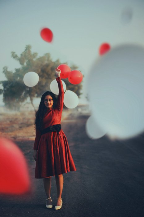 A portrait of a girl in a red dress standing among floating red and white balloons - photo booth ideas