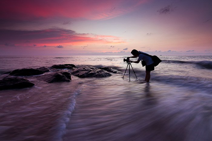 A photographer shooting dratic sky photos on a beach in low light