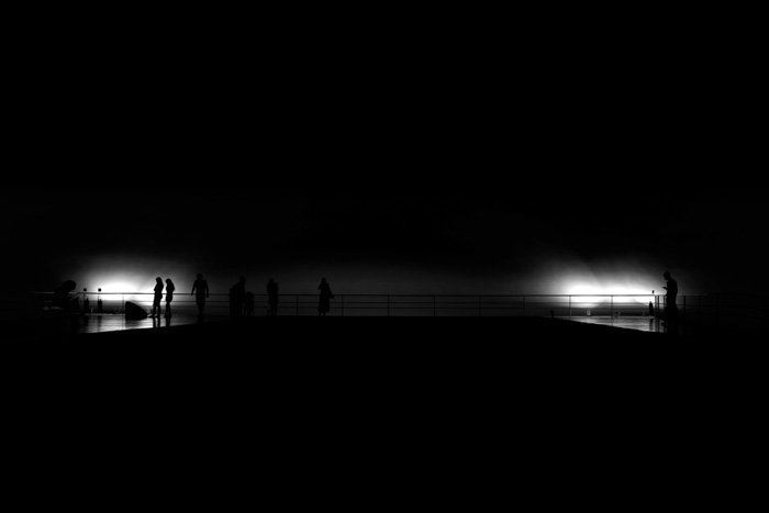 Atmospheric black and white photo of people on a bridge - understanding exposure value