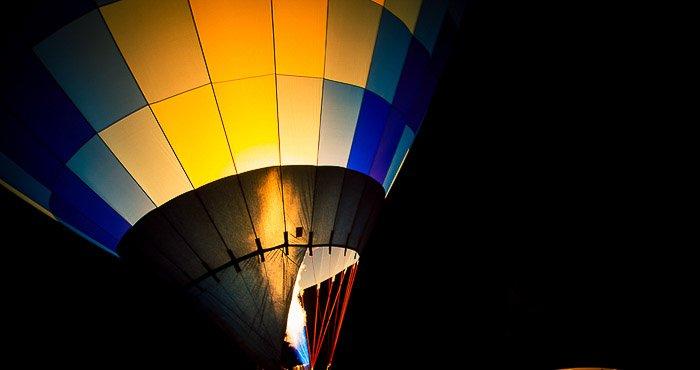 A close up photo of a colorful hot air balloon at night