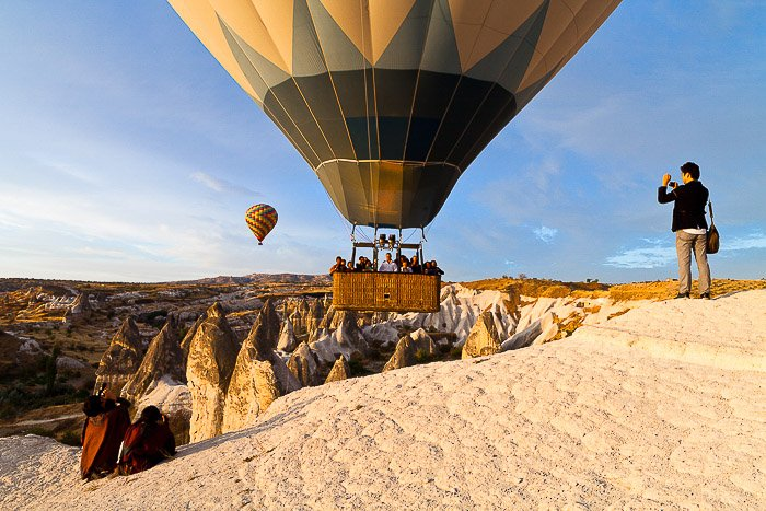 Photographers taking hot air balloon pictures of a balloon just taking off