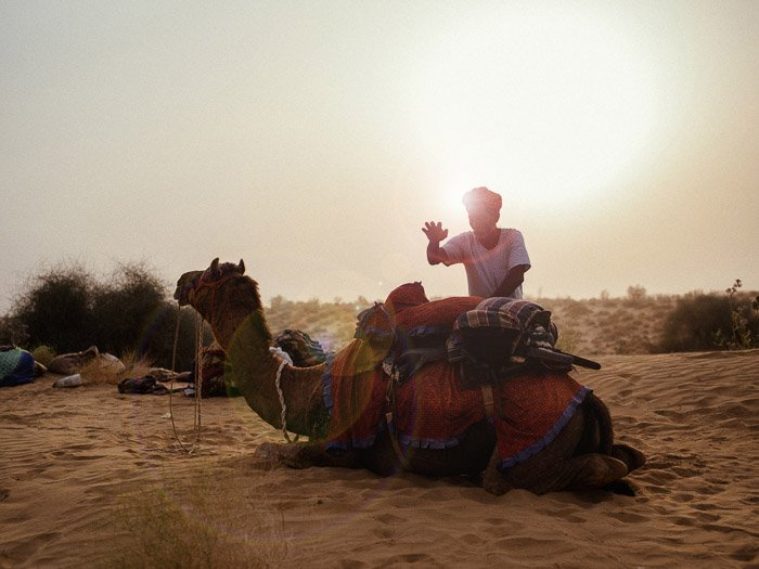 A portrait of a man standing by a camel in the desert, with a beautiful lens flare effect behind him