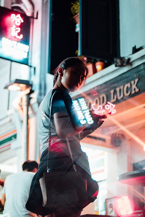 A portrait of a female model surrounded by neon signs