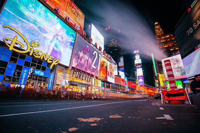 A night street scene filled with the neon lights of store fronts - neon photography tips