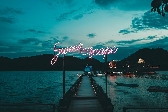 Neon lights reading 'sweet escape' on a tranquil harbour