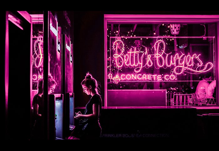 A portrait of a female model surrounded by hot pink neon lights
