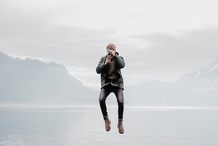 A photographer jumping mid air while taking a photo outdoors - photography assignments