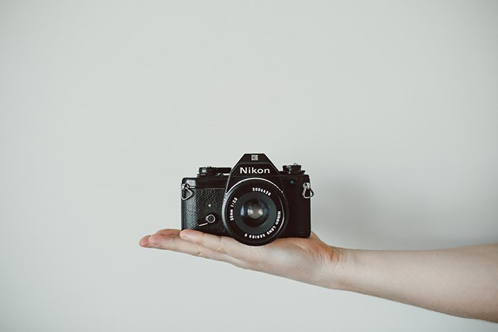 A Nikon Camera balanced on a persons outstretched hand - photography assignments