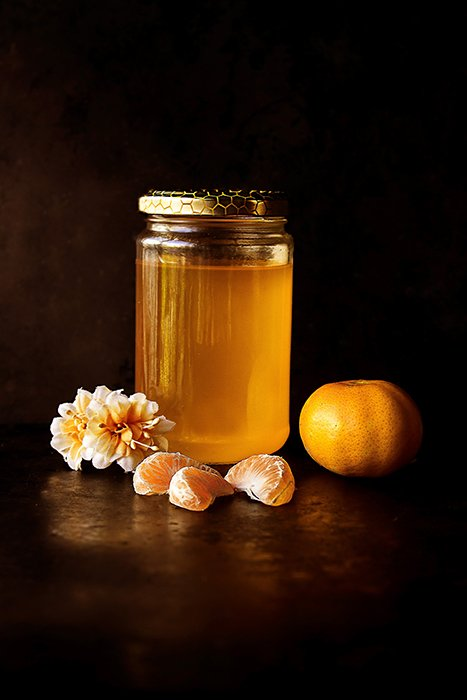 Rustic still life photo of a jar of honey, mandarin segments and flowers against a dark background - photography assignments