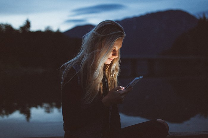 A portrait of a blonde haired woman using her smartphone outdoors in low light
