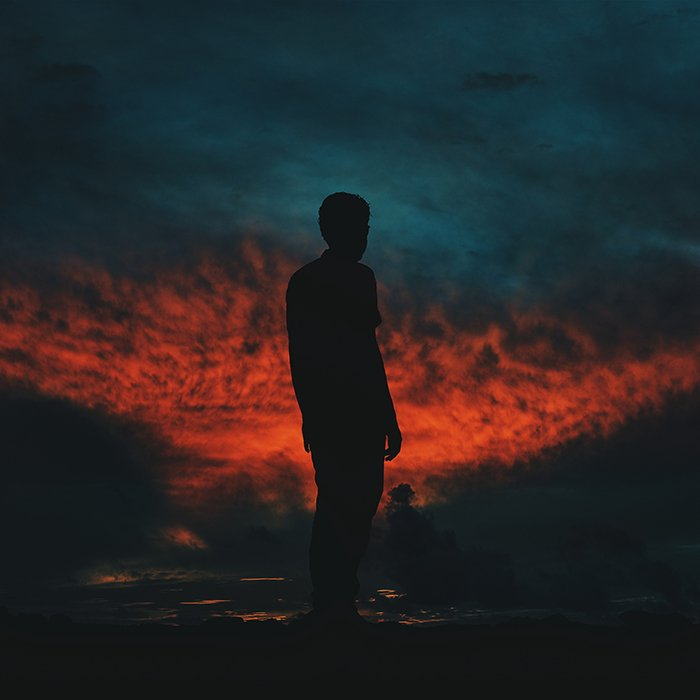 The silhouette of a man against a fiery sky at night - photography assignments