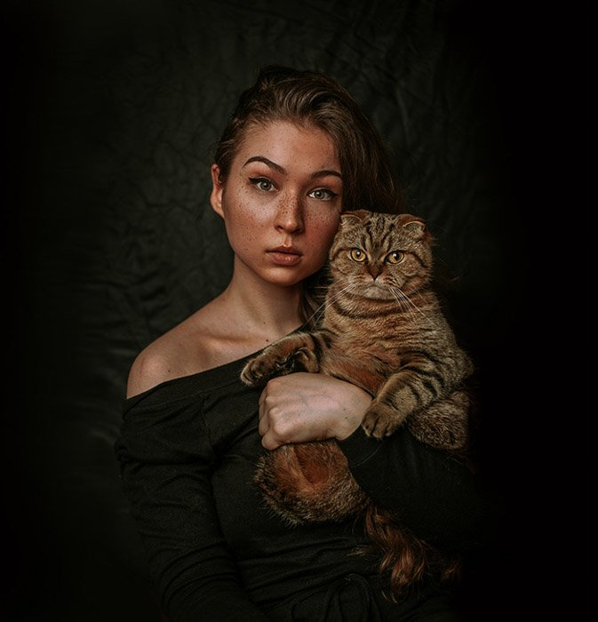 Atmospheric portrait of a female model holding a brown cat