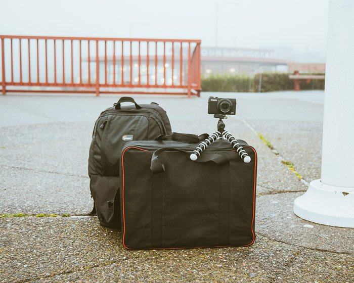 A camera on a small tripod on suitcases