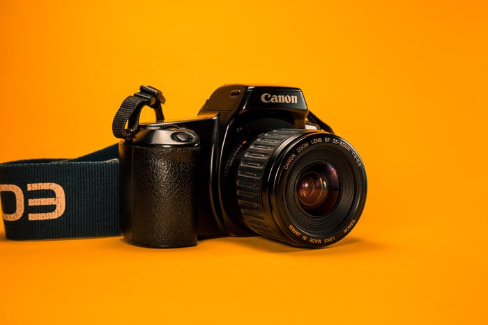 A canon DSLR on a yellow background