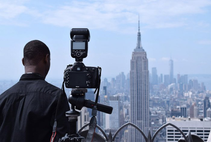 A DSLR set up on a tripod to photograph a cityscape