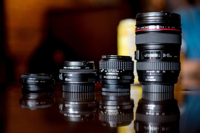 Four different camera lenses on a glass table