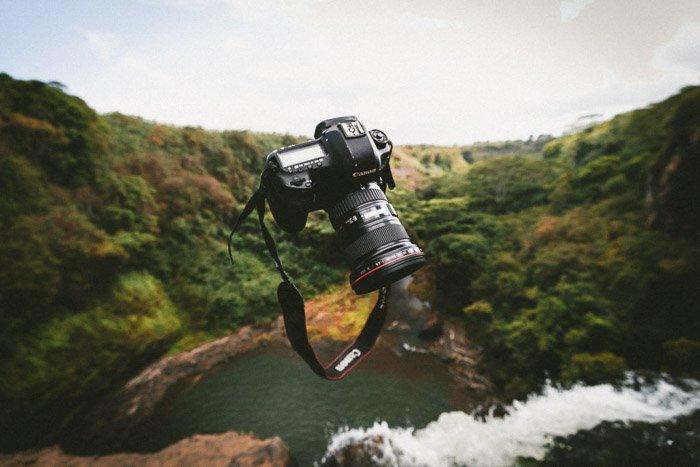 A DSLR camera falling through the air over an impressive landscape