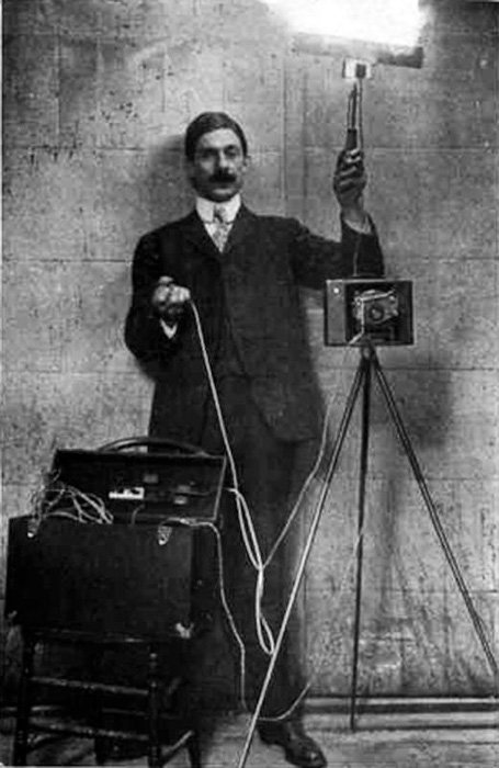 A black and white portrait of a photographer using early flash photography