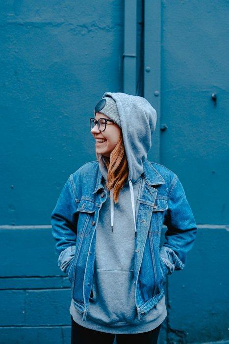 A portrait of a female model posing against a blue wall