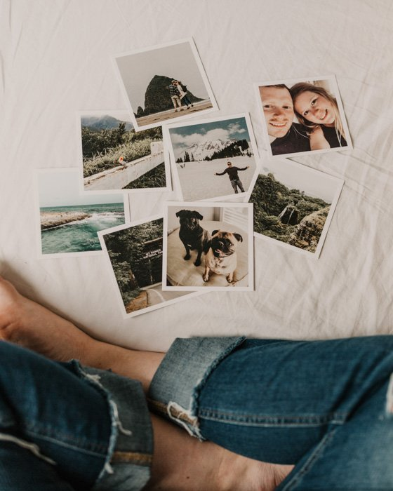 A close up of a person looking at 8 instant camera photos resting on a bed
