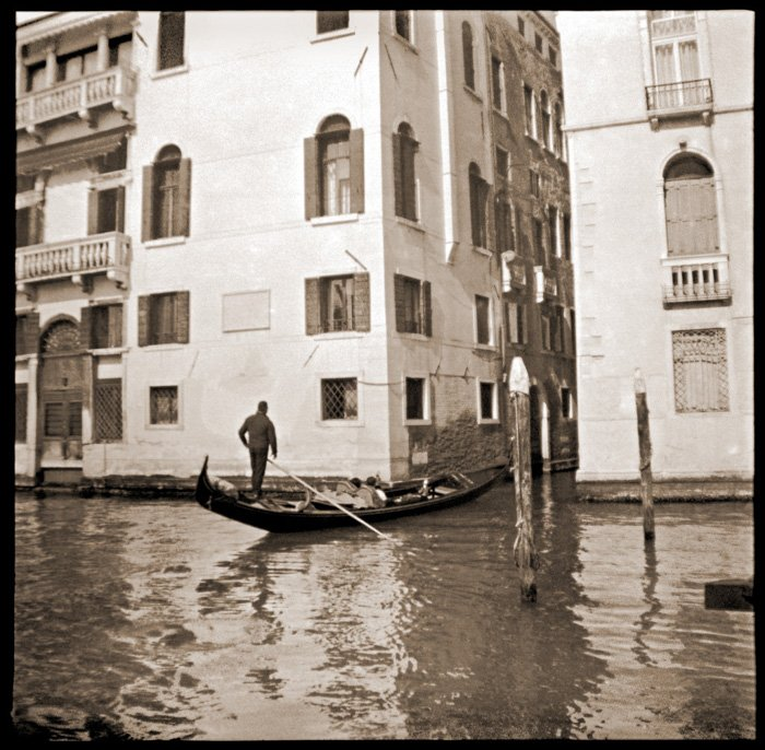 A black and white caffenol photo of a man in a gondola in Venice
